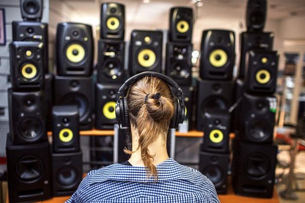 Man met lange paardenstaart zitten voor sound speakers. er zijn er veel in de kamer. jonge man is alleen. Premium Foto