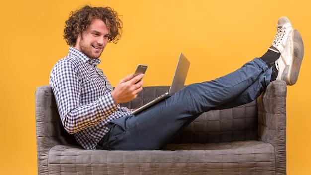 Man met laptop op de bank Gratis Foto