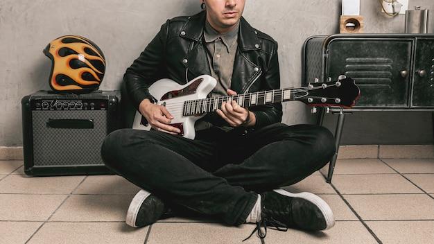Man met lederen jas gitaar spelen Gratis Foto