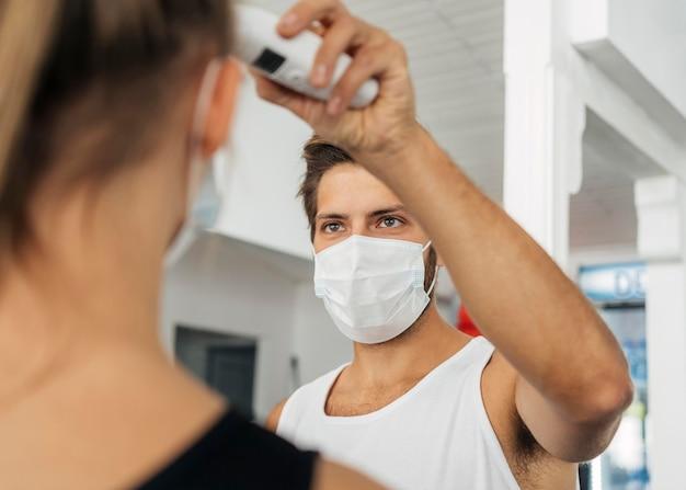Man met medisch masker op de sportschool die de temperatuur van de vrouw controleert Gratis Foto