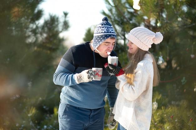 Man met meisje in het bos van de winter met een mok warme dranken Premium Foto