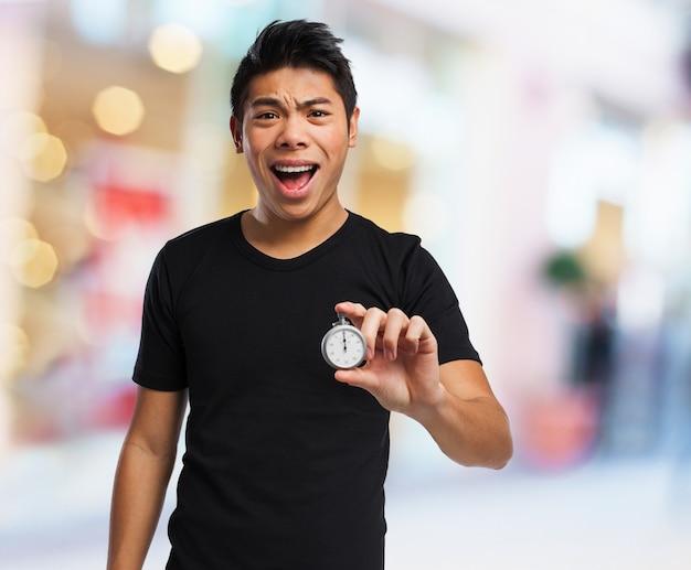 Man met open mond en een klok Gratis Foto