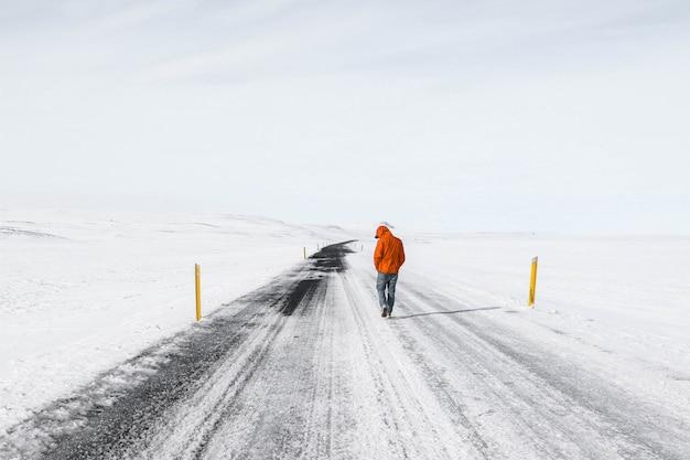 Man met oranje jas wandelen langs een besneeuwde snelweg weg Gratis Foto
