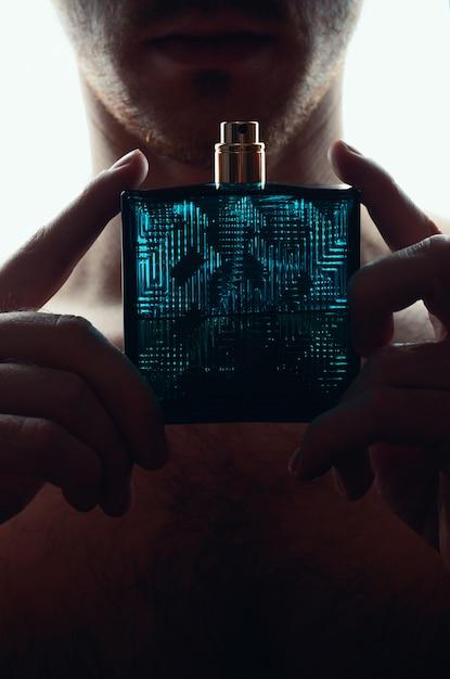 Man met parfum op wit Premium Foto