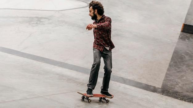 Man met plezier met skateboard buiten in het park Gratis Foto