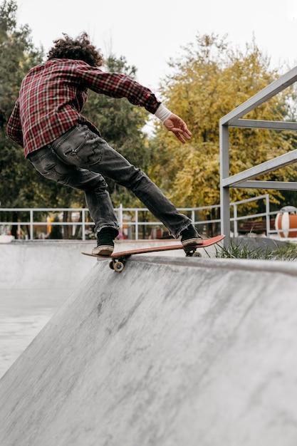 Man met plezier met skateboard in het park Gratis Foto