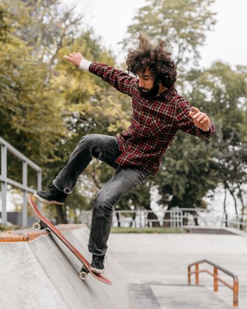 Man met plezier met skateboard in het stadspark Gratis Foto