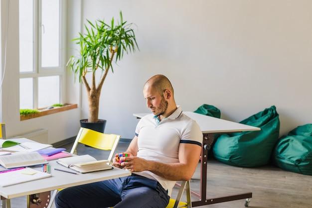Man met puzzel tijdens studies Gratis Foto