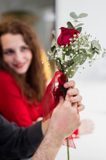 Man met rode roos tak in de hand Gratis Foto