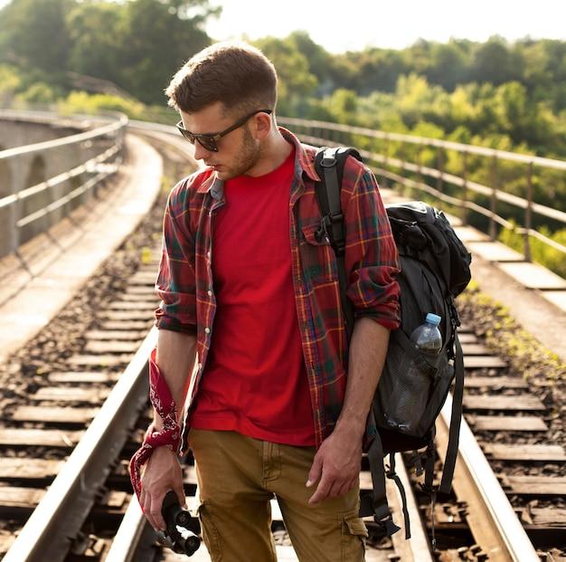 Man met rugzak op treinrail Gratis Foto