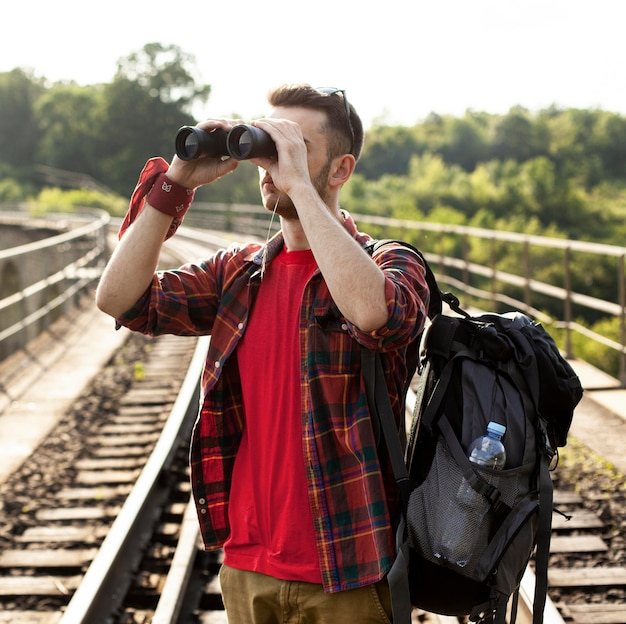 Man met rugzak op zoek met verrekijker Gratis Foto
