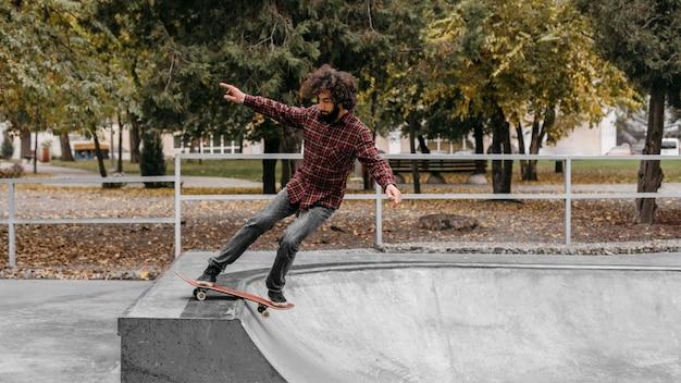 Man met skateboard buiten in het park Premium Foto