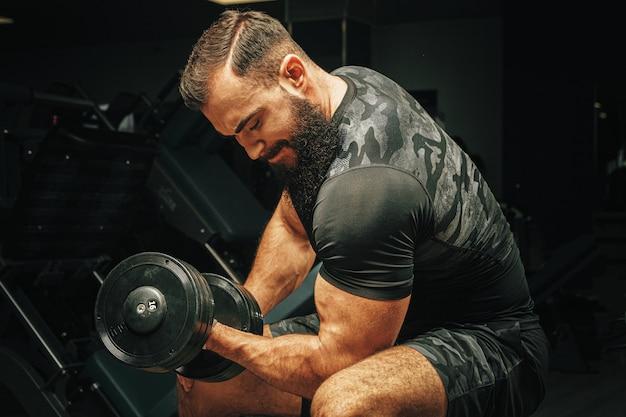 Man met sport lichaam opheffing halters in de sportschool Premium Foto
