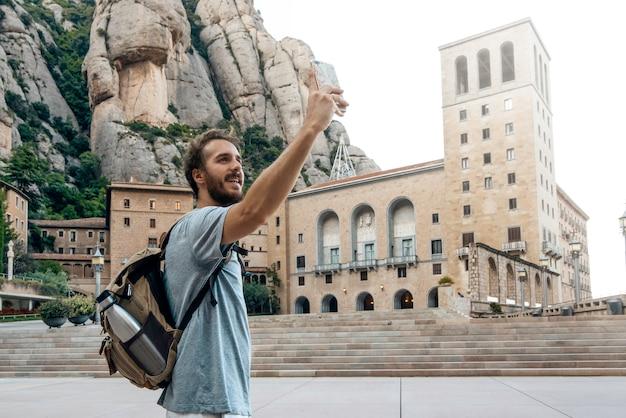 Man met telefoon die een selfiefoto neemt in het klooster van montserrat, barcelona, spanje Premium Foto