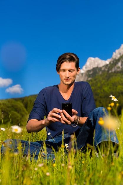 Man met telefoon zit in de bergen Premium Foto