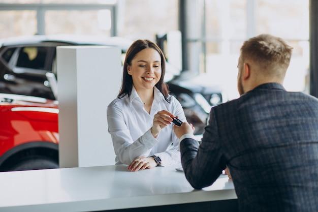 Man met verkoopvrouw in autoshowroom Gratis Foto