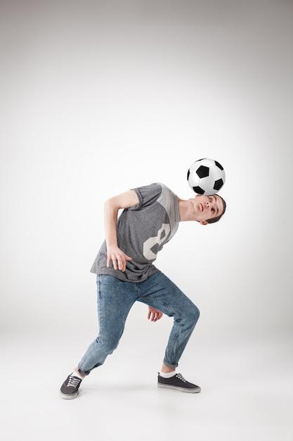 Man met voetbal op grijs Gratis Foto