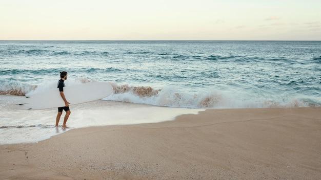 Man met zijn surfplank afstandsschot Gratis Foto