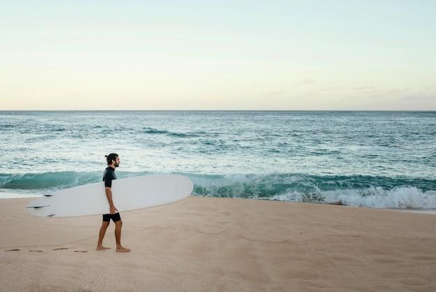Man met zijn surfplank naast de oceaan Gratis Foto