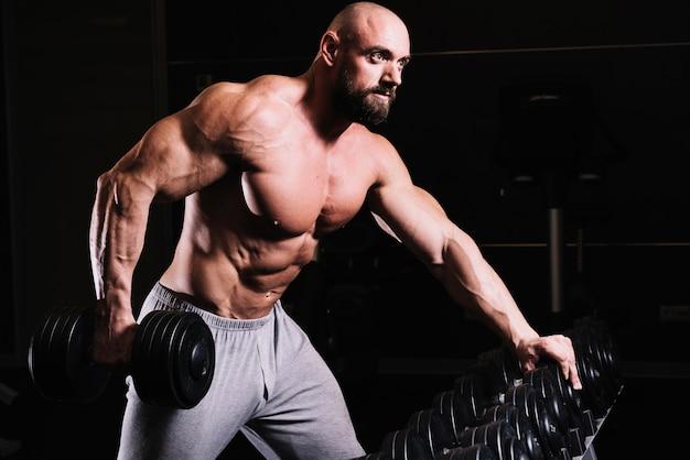 Man met zware halter in de buurt van rek Premium Foto