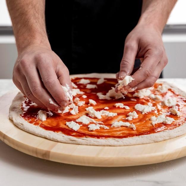 Man mozzarella op pizzadeeg zetten Gratis Foto