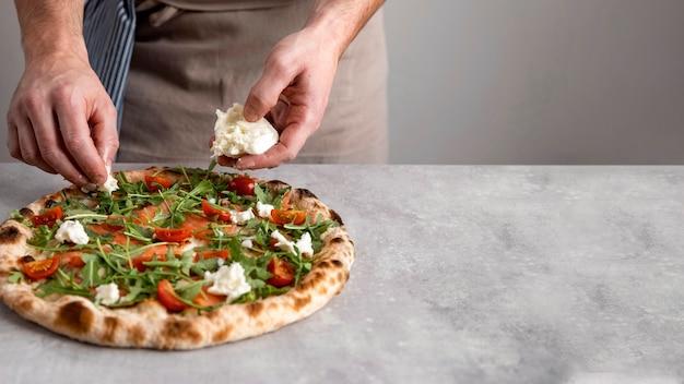 Man mozzarella zetten gebakken pizzadeeg met plakjes gerookte zalm Gratis Foto