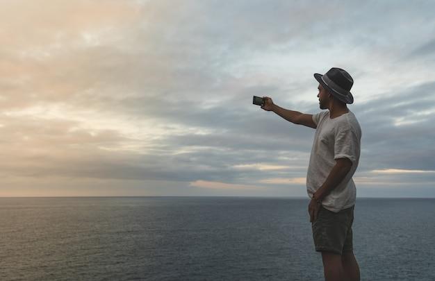 Man neemt een foto naar de oceaan bij zonsondergang. Premium Foto