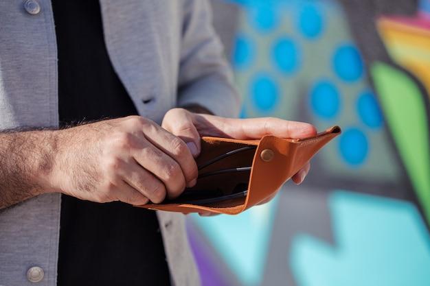 Man neemt geld uit zijn portemonnee Gratis Foto