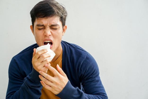 Man niezen na krijgen allergie of griepvirus en het gebruik van papieren zakdoekje voor vegen op de neus Premium Foto