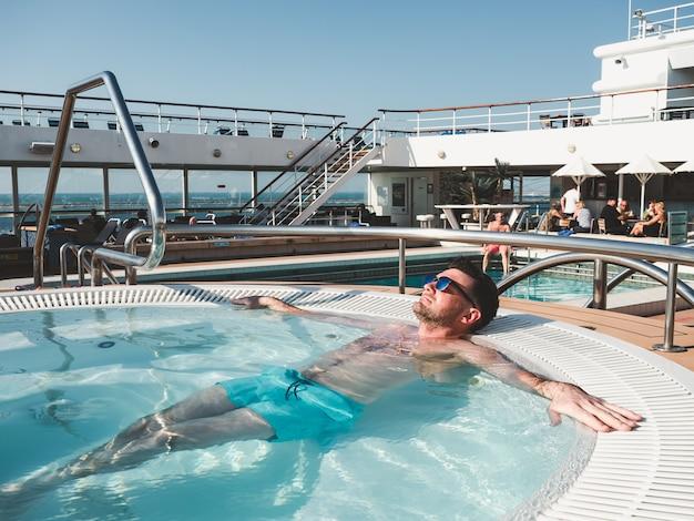 Man ontspannen in het zwembad op het dek Premium Foto