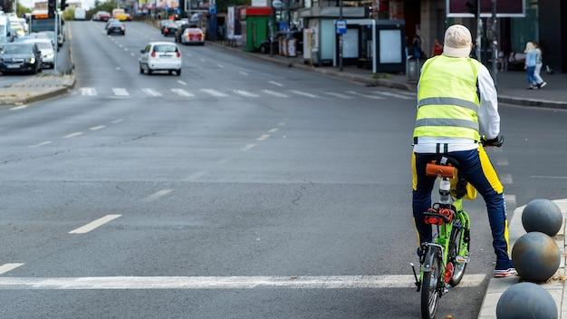 Man op de weg op een kleine groene fiets, straat met auto's en mensen Gratis Foto