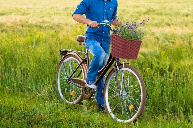 Man op een fiets met bloemen in een mand Premium Foto