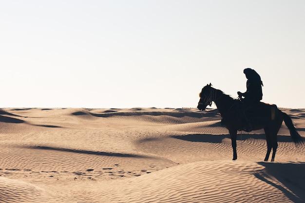 Man op een paard in de woestijn. Premium Foto