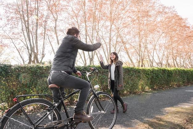 Man op fiets groet vrouw in park Gratis Foto