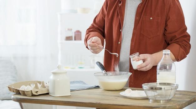 Man op middelbare leeftijd pannenkoekdeeg kneden op witte keuken Premium Foto