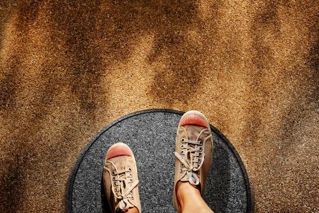 Man op sneaker schoenen stappen over cirkellijn naar buiten gebonden Premium Foto