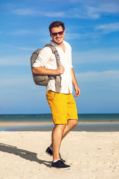 Man op strand glimlachend en gelukkig hipster heldere outfit dragen. jong mannelijk model dat van de zomervakantie geniet door de oceaan met modieuze rugzak Gratis Foto