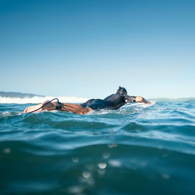 Man op zijn surfplank zwemmen Gratis Foto