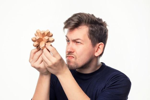 Man op zoek verward houten puzzel. Gratis Foto