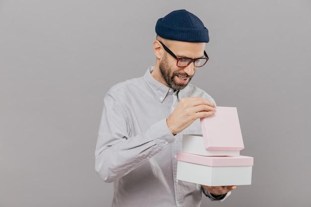 Man opent geschenkdoos, kijkt nieuwsgierig, draagt een bril, hoed en wit shirt, staat tegen een grijze achtergrond Premium Foto