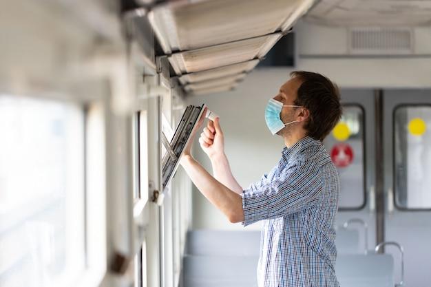 Man opent raam in trein om frisse lucht en ventilatie in te ademen en draagt beschermend masker tijdens nieuwe normale verandering na covid-19-uitbraak Premium Foto