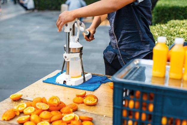 Man perst sinaasappelsap buitenshuis Premium Foto