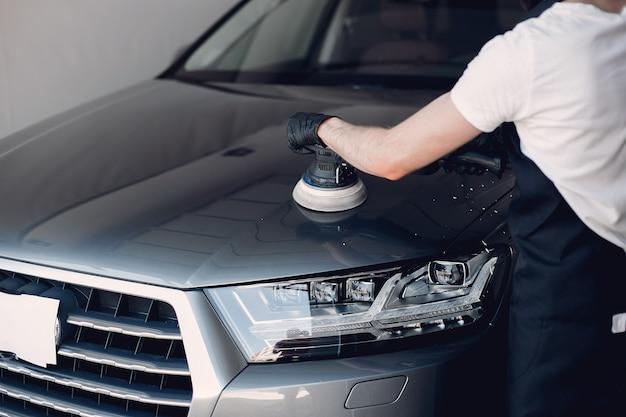 Man polijsten een auto in een garage Gratis Foto