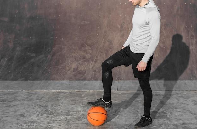 Man poseren met een basketbal aan zijn voeten Gratis Foto