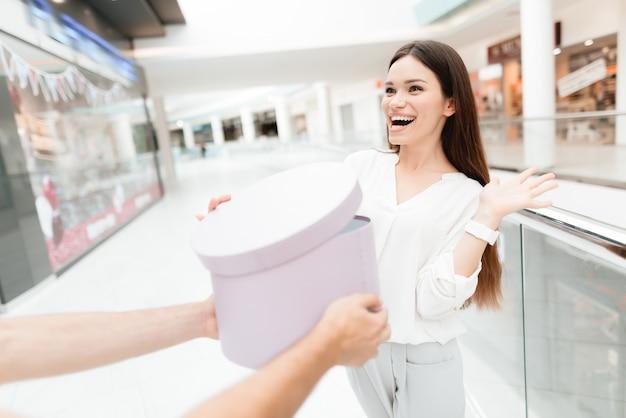 Man presenteert vrouw met nieuwe ronde doos met aankoop. Premium Foto