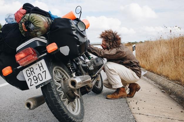 Man probeert motor langs de weg te repareren Gratis Foto