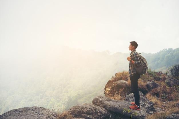 Man reiziger met rugzak op de top van de berg. reis lifestyle concept. Gratis Foto