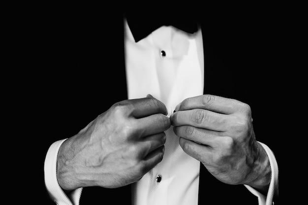 Man repareert knoppen op zijn witte shirt Gratis Foto
