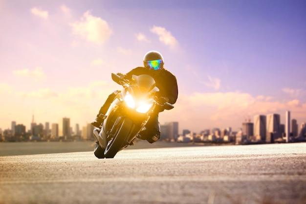 Man rijden sport motorfiets leunen op kromme weg tegen stedelijke skyline Premium Foto