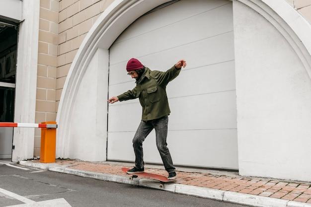 Man rijdt zijn skateboard buiten in de stad Gratis Foto